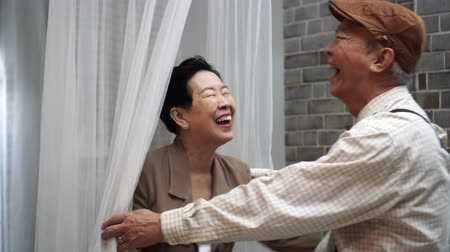 sepia : Asian senior elderly play laugh have fun together hide and seek behind net Stock Footage