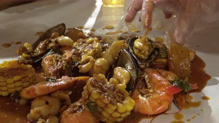 molho : Seafood bucket boil in new orleans spice sauce eating with hand 4k