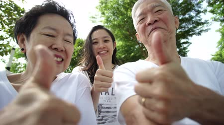 gestos : Asian family senior and daughter giving thumb up happy gesture