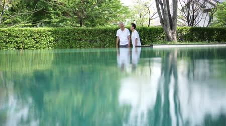отступление : Asian Elderly Couple Walk Around Resort Pool Copy Space