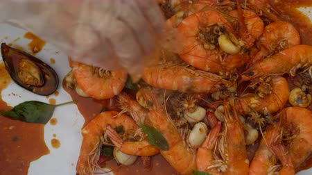 shellfish dishes : Seafood Bucket Prawn With Red Cajun Sauce Hand Eating With Plastic Glove