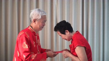 nimet : Chinese Senior Couple Give Out New Year Red Envelop Stok Video