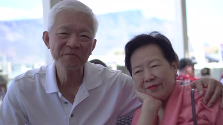 пожилые : Asian senior couple travel to Cape Town, South Africa happy at restaurant