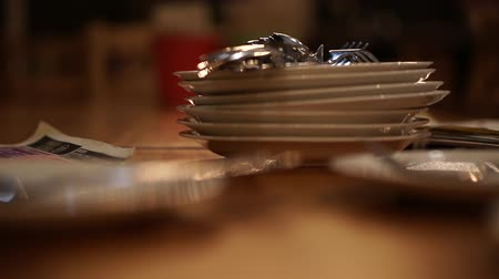 settings : Pile stack of white ceramic plates at hip restaurant at night Stock Footage