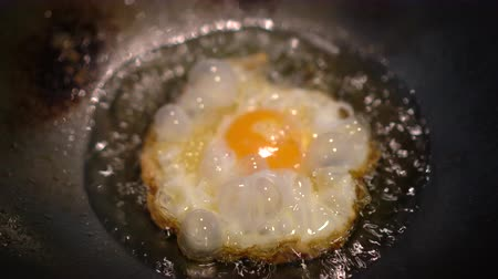 cholesterol : Asian Thai style fries egg in oil iron wok Stock Footage