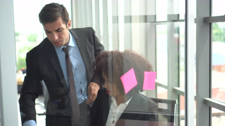 placa : African and Hispanic coworker discuss brainstrom sticky note board