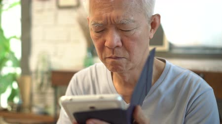 grey eyes : Asian elderly with bad eyesight can not see when using tablet
