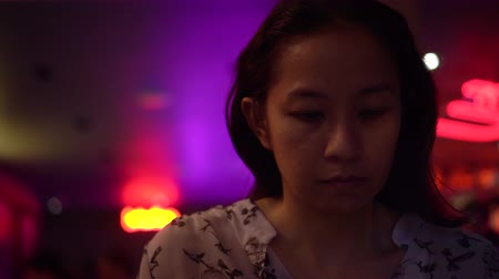 bad mood : Asian woman using phone at night neon bar Stock Footage