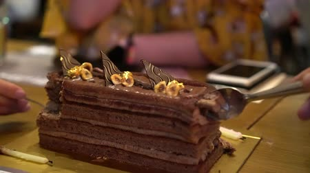 négyszögletes : Friends eating chocolate square cake layers ganache together