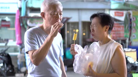 savanyú : Asian senior couple eating pineapple vitamin tropical fruits Stock mozgókép