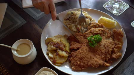 migalha : Eating pork Schnitzel Austria cuisine battered meat with  Sauerkraut and potatoes Stock Footage