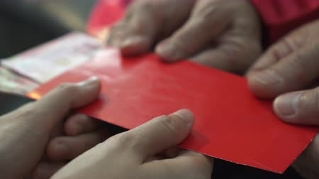 давать : Hands parents giving red envelop and money to children for Chinese New Year close up