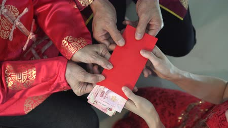 лунный : Hands parents giving red envelop and money to children for Chinese New Year close up
