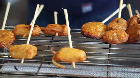 fish ball : Hands grilling squid balls on electric grill in Japanese market Stock Footage
