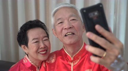 cultura tradicional : Chinese elder coupl selfie in New Year theme technology to stay connect
