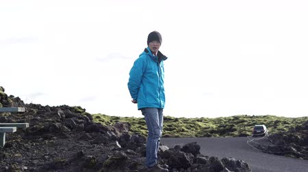 magma : Asian man have fun in Iceland with mossy volcanic landscape