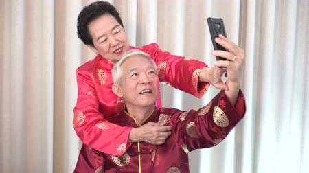 travel theme : Chinese elder coupl selfie in New Year theme technology to stay connect