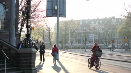 голландский : Amsterdam, Netherland - 4 Apirl 2017: morning sun at local city street side walking and biking