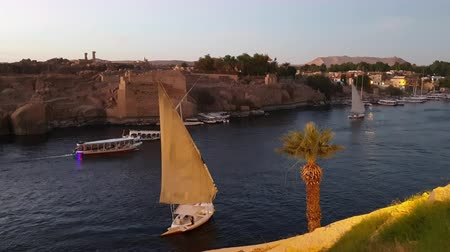 Felucca boat sailing in Nile river of Egypt sunset with background