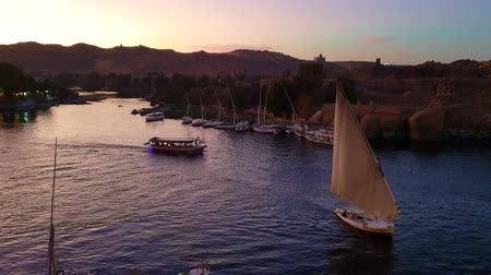 Нил : Felucca boat sailing in Nile river of Egypt sunset with background