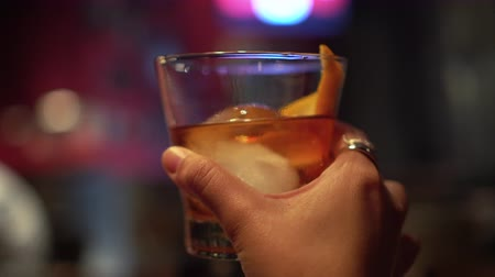 bourbon whisky : Hand holding old fashioned cocktail rum and orange on the circular ice Stock mozgókép