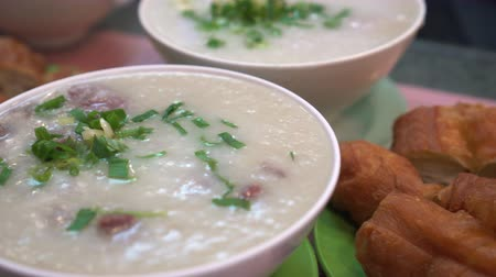 zabkása : Eating Hong Kong Cantonese congee bowls and dough sticks Stock mozgókép