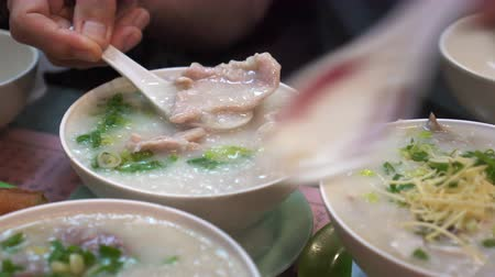gruel : Hands eating Hong Kong Cantonese congee bowls and dough sticks Stock Footage