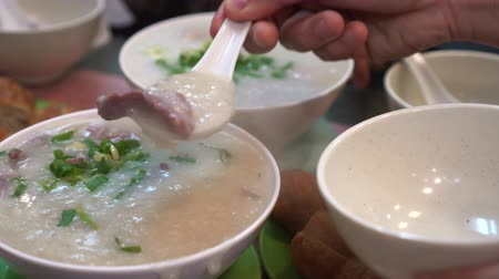 gruel : People eating Hong Kong Cantonese congee bowls and dough sticks Stock Footage