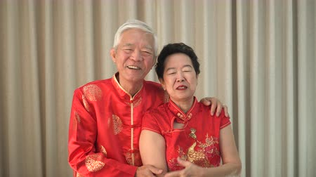 Asian senior couple celebrating Chinese New Year wearing red costume