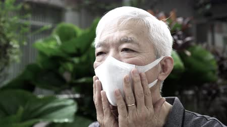 Asian Chinese elder wearing N95 mask protection from smog and Coronavirus