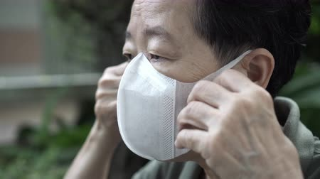 tosse : Close up Asian Chinese elderly wearing protection mask with worry expression for virus spread Stock Footage