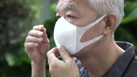 tosse : Close up Asian Chinese elderly wearing protection mask with worry expression for disease spread Stock Footage