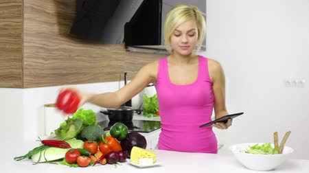 yemek tarifi : young pretty girl looking recipe prepare dinner Stok Video