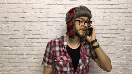 nerd : man smart phone call, smile guy hipster talking fashion style wearing hat glasses over white brick wall
