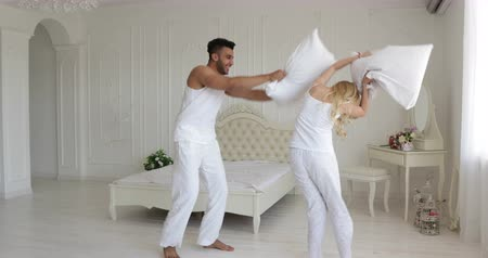 almofada : Couple fighting pillows bedroom mix race man woman playing having fun together