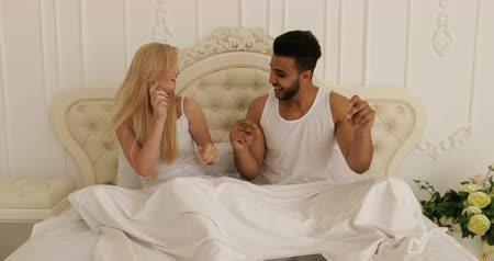 genç çift : Couple Sitting bed dancing mix race man woman playing having fun together bedroom Stok Video