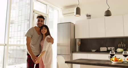 daireler : Young Mixed Race Couple Modern Apartment Big Window Morning Sunlight, Cute Happy Hispanic Man And Asian Woman Embracing Slow Motion