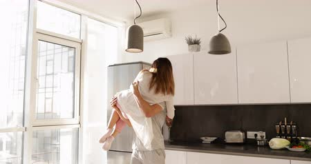transportar : Happy Smiling Man Carry Asian Woman, Young Romantic Couple Together In Kitchen Slow Motion