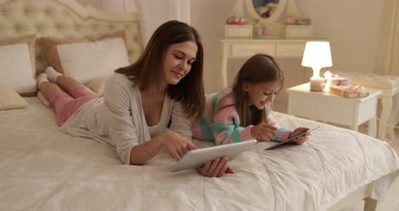 время ложиться спать : Mother With Daughter Lying On Bed Using Tablet Computer Happy Young Family Small Girl And Woman Bedroom Стоковые видеозаписи