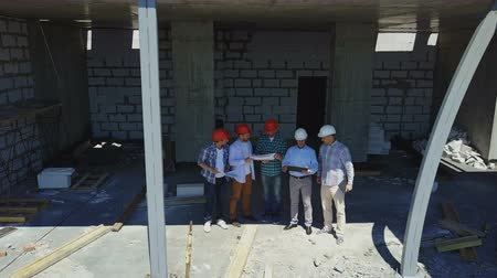stavitel : Aerial Shot Of Builders Team On Construction Site Discussing Plan Of Project With Architect And Contractor Using Blueprint On Digital Tablet