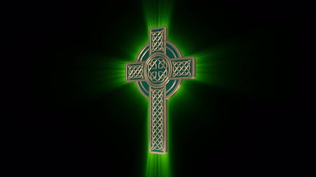 kelt : Celtic Gold Cross with green glowing rays rotates around an axis on a black background. Seamless looping