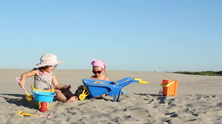 ásta : two little girls playing in sand