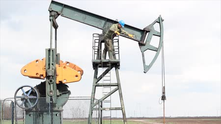 oil industry : oil worker standing at the pump jack