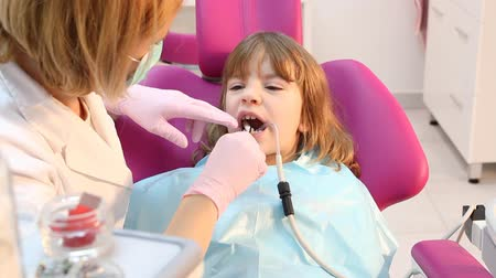 капелька : beautiful little girl with open mouth during drilling treatment at the dentist