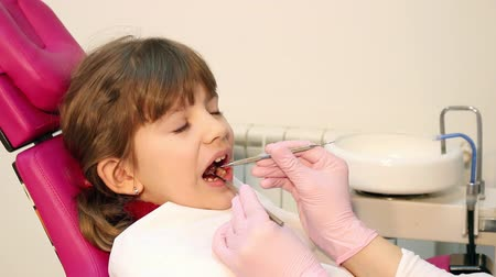 little : little girl checks teeth at the dentist