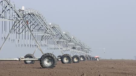farm equipment : center pivot sprinkler system moving on field Stock Footage