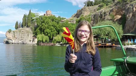 ohrid : happy little girl waves with a Macedonian flag on Ohrid lake