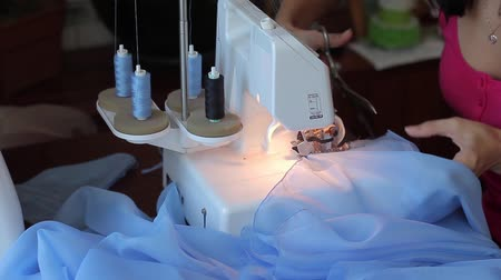 kostüm : Beautiful woman sewing finishes. Powered by overlock. scissor Stok Video