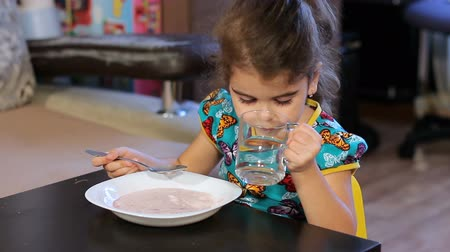 búzadara : The girl begins to eat porridge. Washed down with a glass of water.
