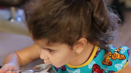 búzadara : Little girl greedily eating semolina porridge. Wash down with water from a transparent glass. closeup.